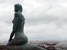 Die Meerjungfrau blickt auf das Meer hinaus.