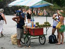 Kurz vor dem Eingang vom Manuel Antonio Nationalpark verkauft ein Händler Kokosnüsse.