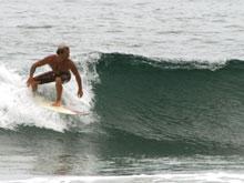 Un surfista en una pequeña ola en Playa Junquillal.