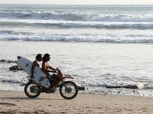 Dos surfistas andan en una motocicleta para llegar a su siguiente sesión de surf.